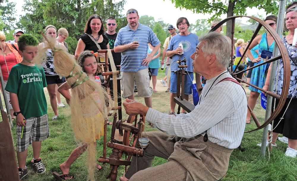 an elderly man demonstrating wool working to children