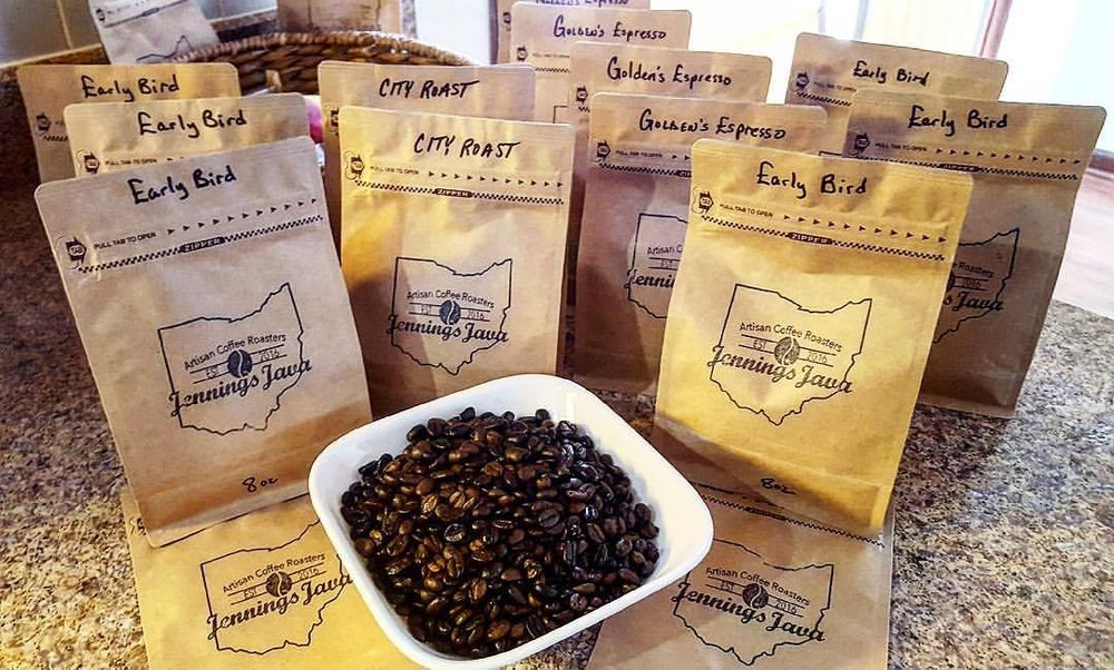 Packaged coffee from Jenning's Java with a bowl of beans sitting in front of them