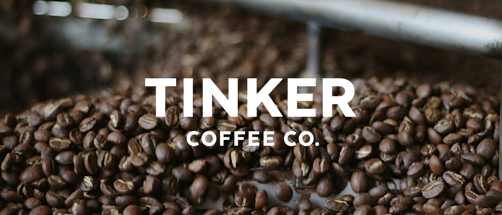 """Coffee beans from Tinker, with """"Tinker Coffee Co."""" overlaid on the image in white text"""