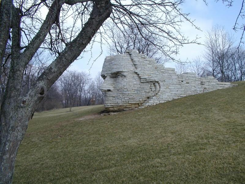 a white brick sculpture of chief leather lips set into a hillside in dublin ohio
