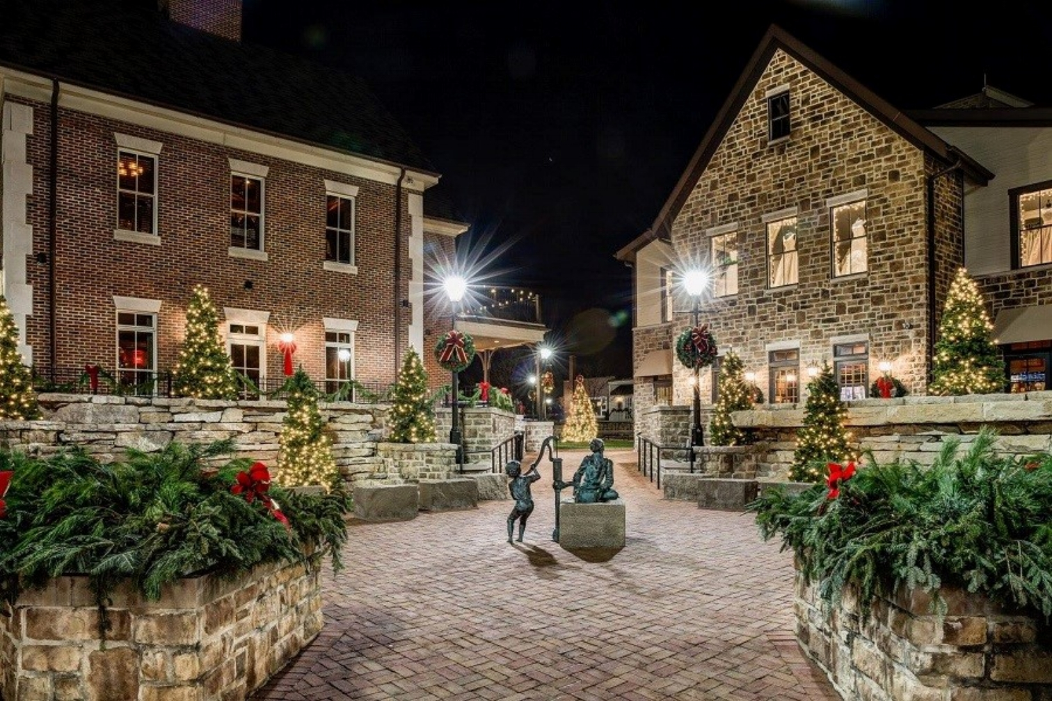 A cobblestone street with two historic brick buildings aglow with decorated christmas trees and planters full of red poinsettia flowers