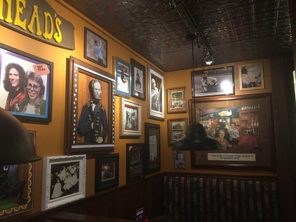 photographs and portraits of various celebrities line the orange walls of cherry street pub in lancaster, OH