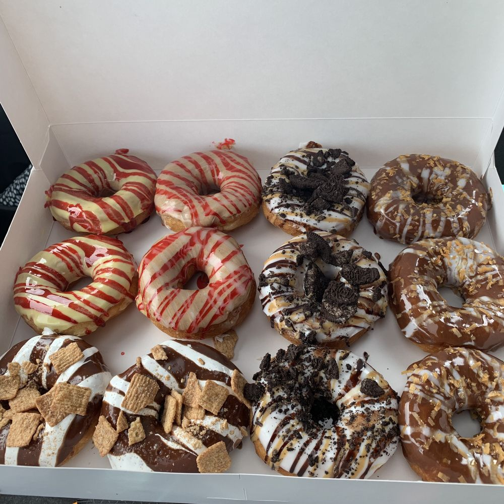 A box of donuts from Dough-Hio Donuts in Lancaster, OH, including yellow donuts with yellow icing and red drizzle, white icing with oreo crumbs, and chocolate icing with cinnamon toast crunch cereal.