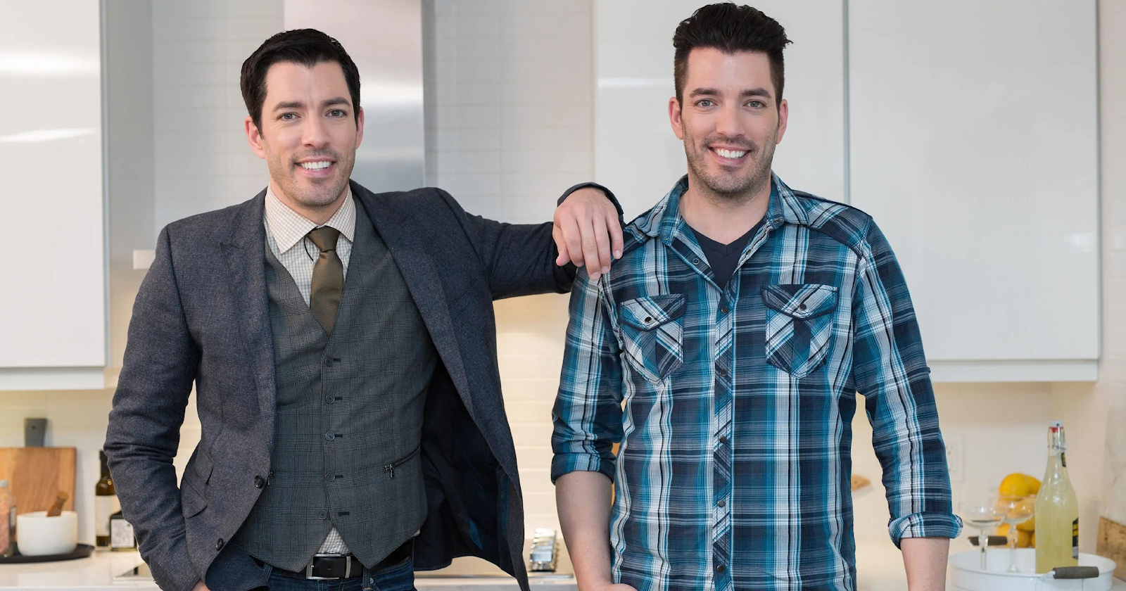 Drew Scott in a three-piece suit and Jonathan Scott in a flannel button-down stand side by side in immaculate white kitchen