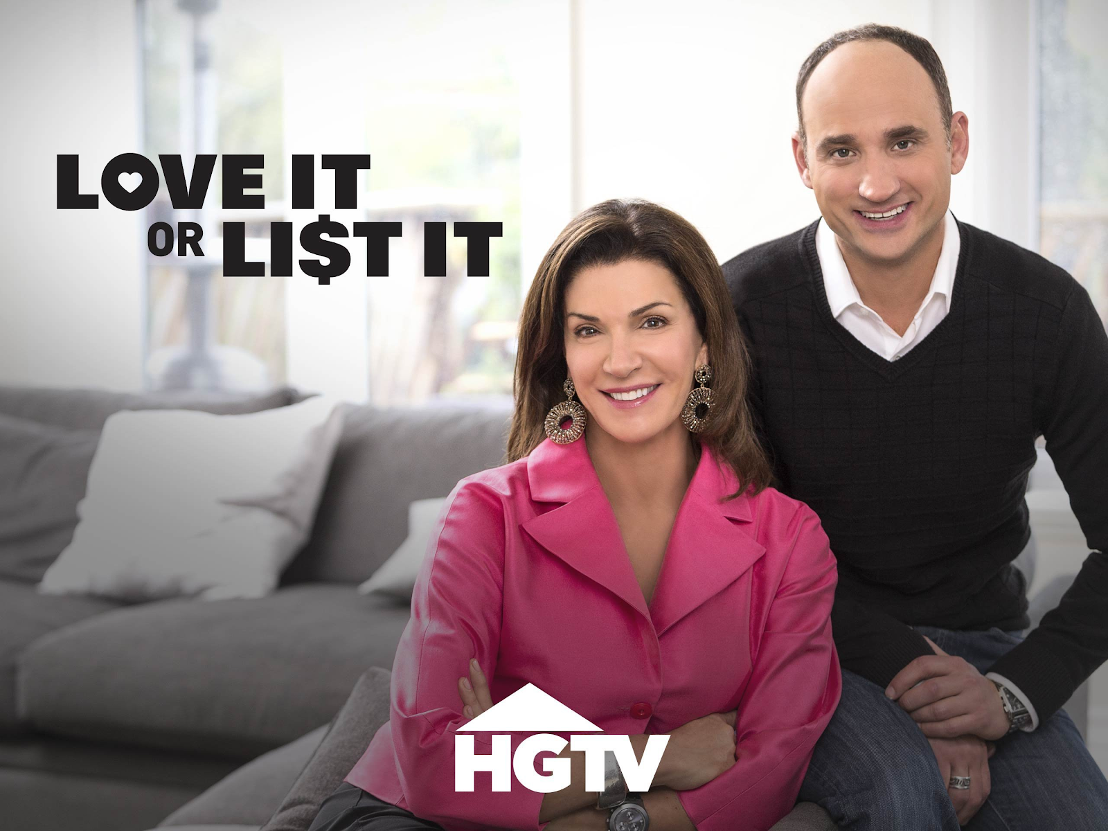 Hilary Farr and David Vesentin sit side by side smiling on a couch