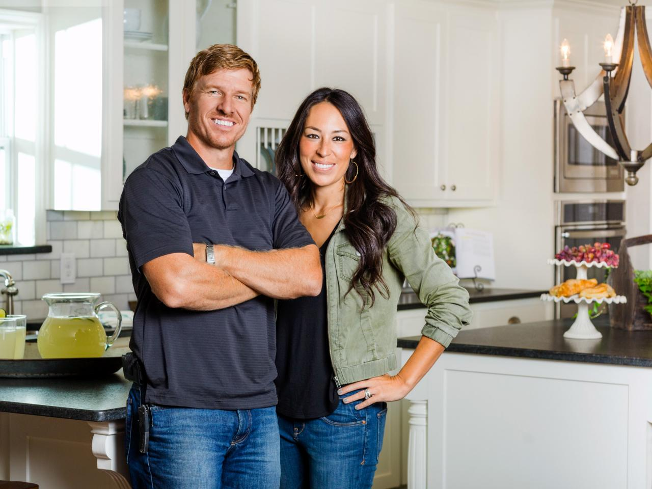 Joanna and Chip Gaines stand side by side smiling in an immaculate white and black kitchen