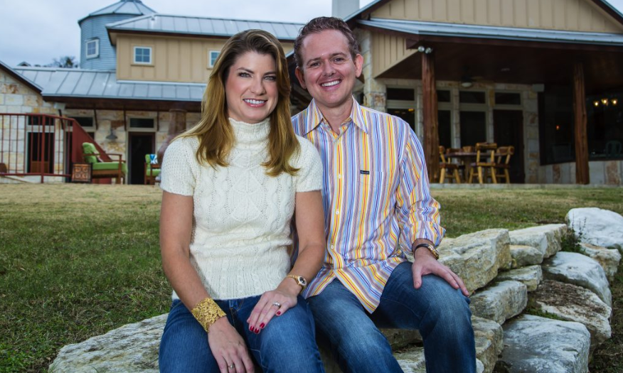 Tim and Julie Harris sit and smile outdoors in front of an industrial-looking country home