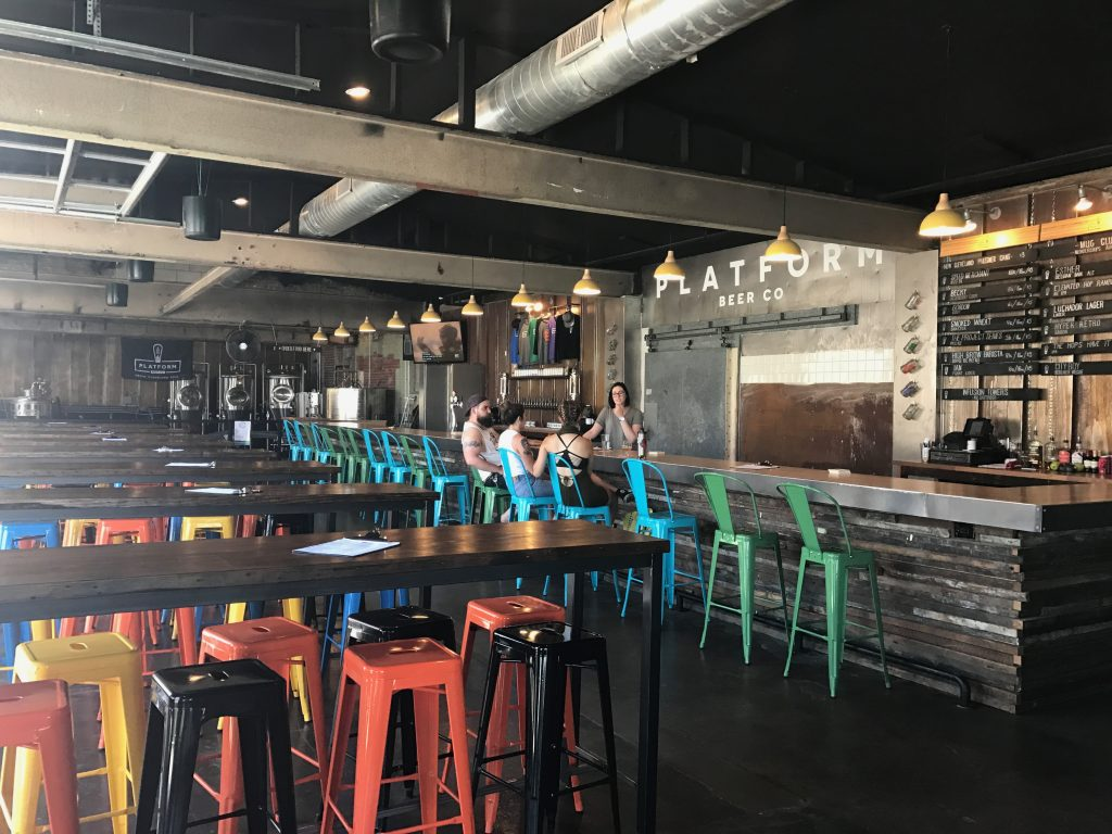 Three young adults sit at bar in Platform Beer taproom as bartender takes orders