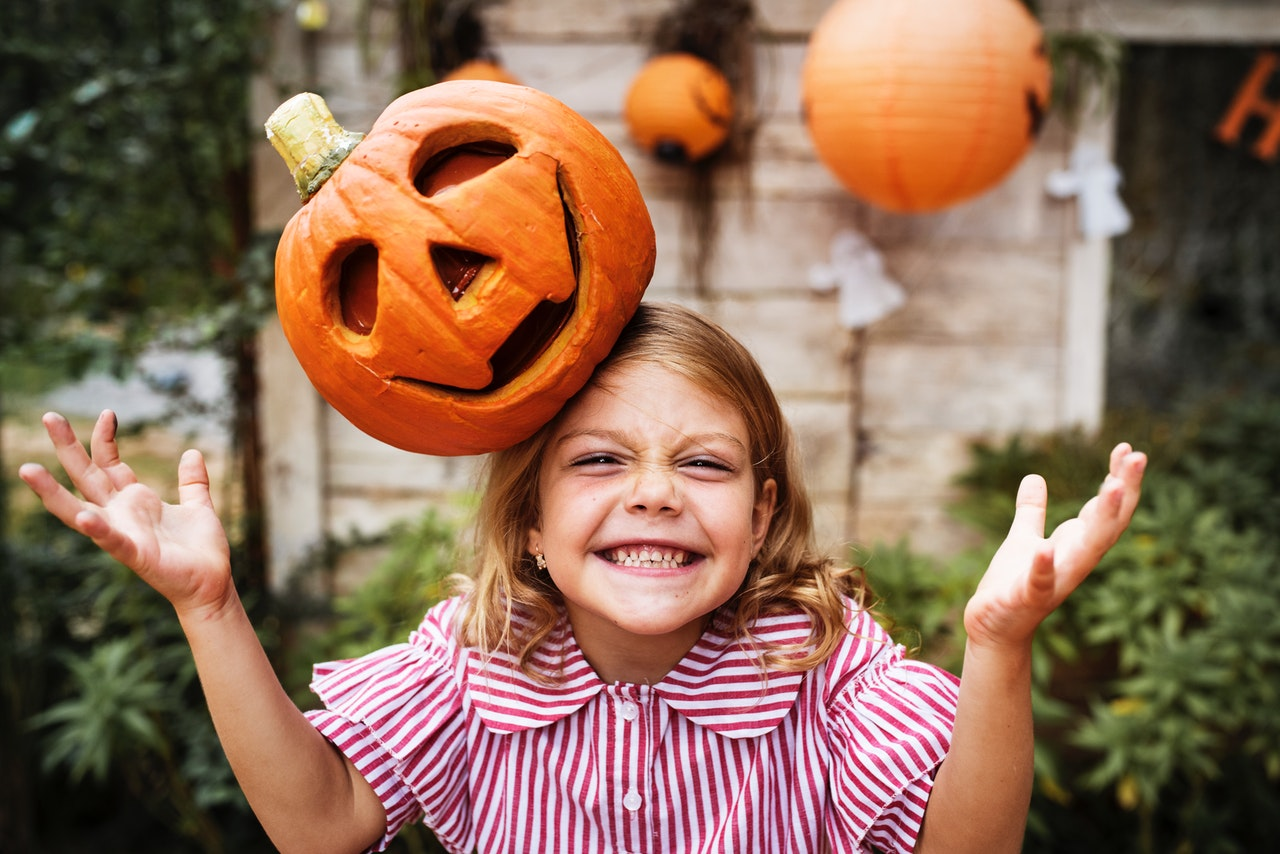 a young girl with a jack o lantern on her head as part of a halloween costume