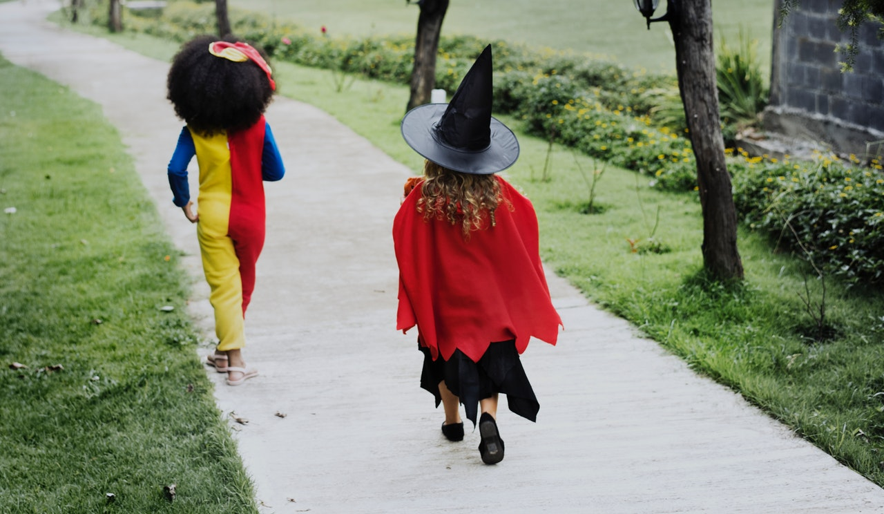 A child in a clown costume and a child in a which costume run down a sidewalk, excited to trick or treat on halloween.