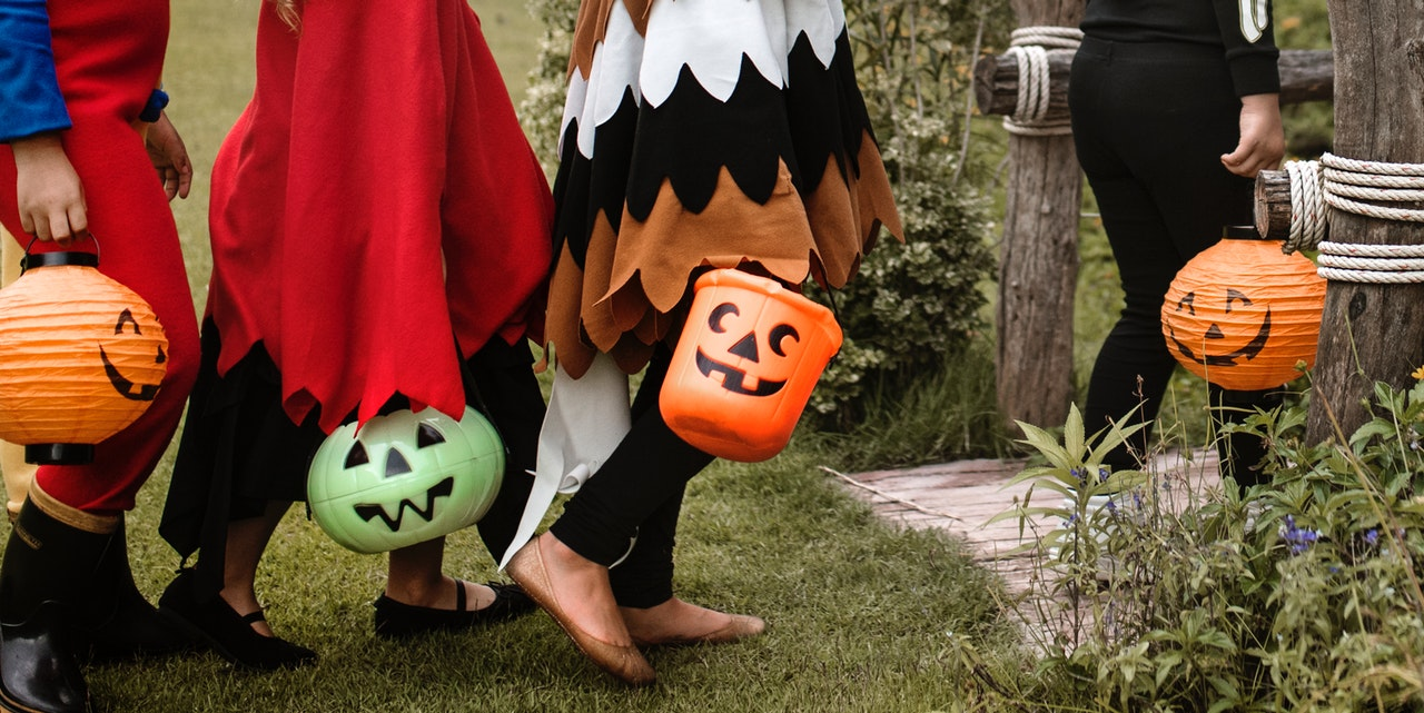 Children holding candy pails shaped like jack-o-lanterns march towards their trick-or-treats