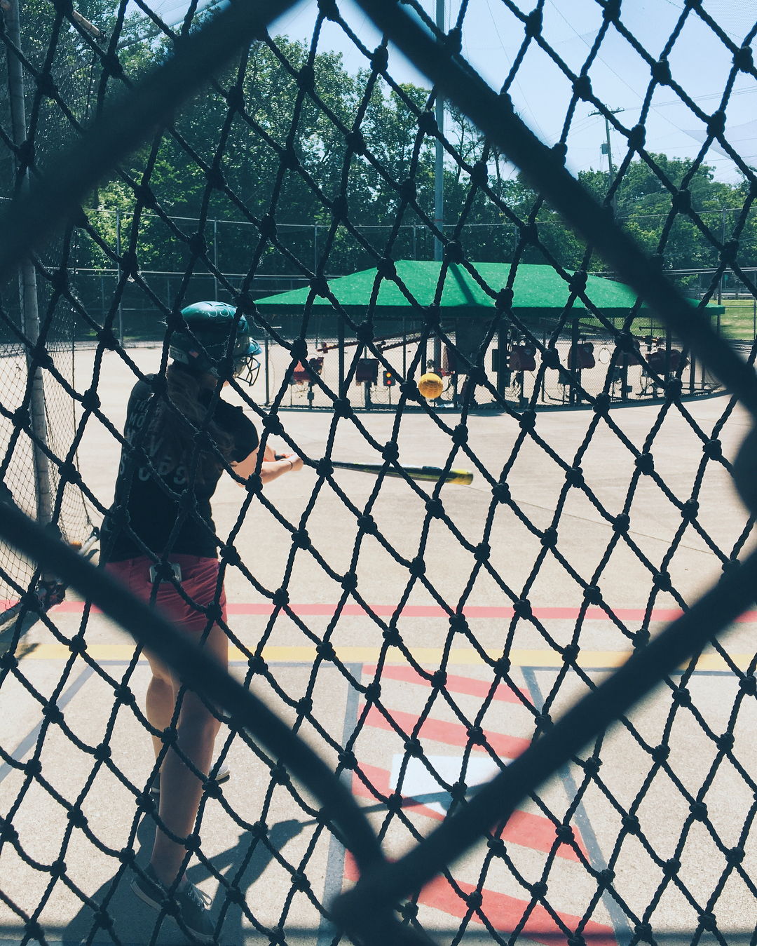 Boy hits ball in batting cage