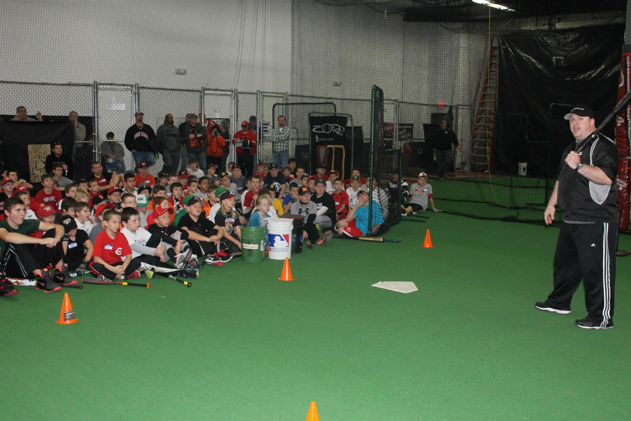 A class full of children being lectured on batting