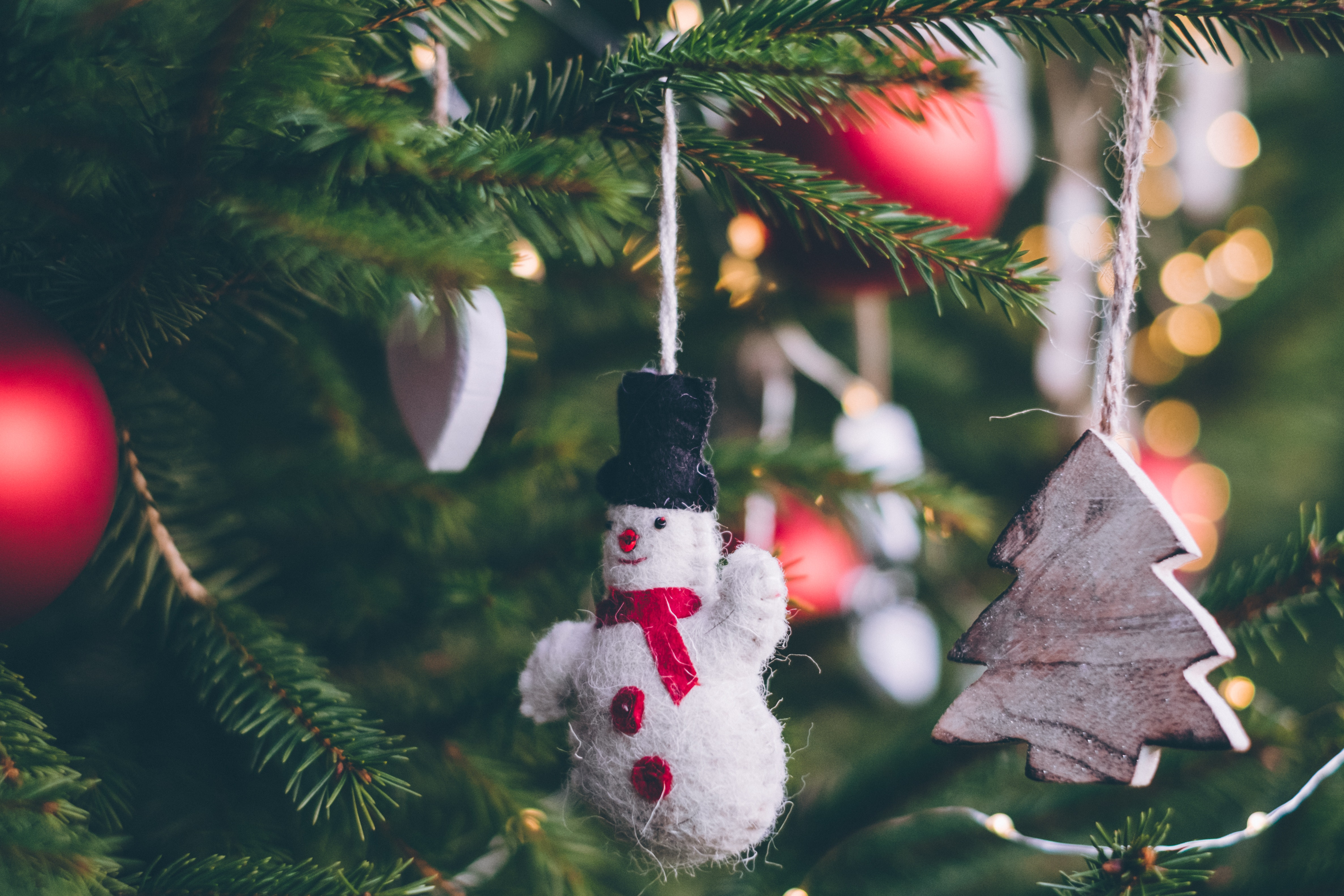 Snowman hanging from a tree with red ornaments
