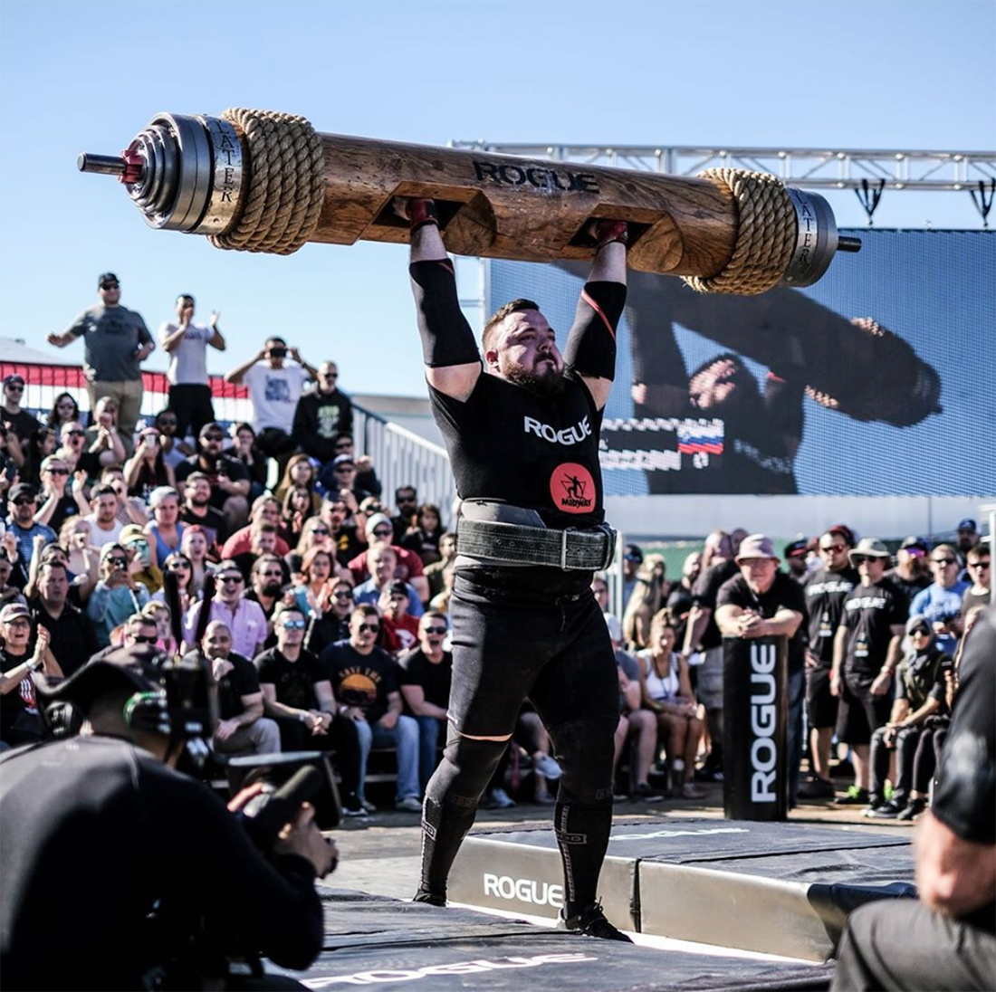 Strong man lifting heavy weights in front of a crowd