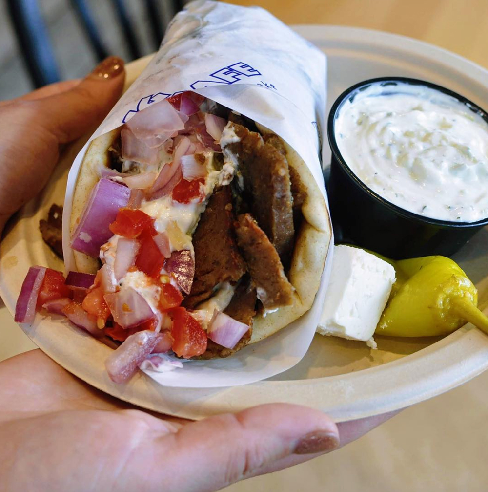 A gyro on a plate with pepper and tatziki