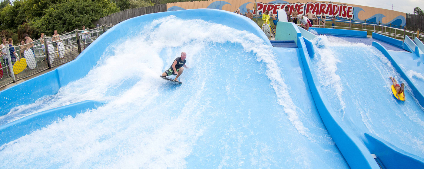 A man is boady board surfing on a large water slide