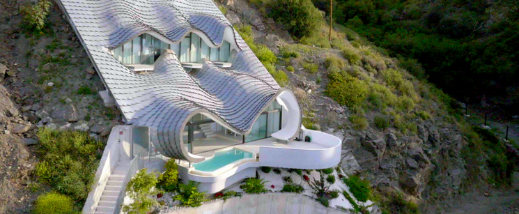 A white house with a pool built into a mountain.