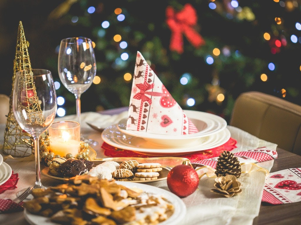 A Christmas place setting with a tree in the backgroundw