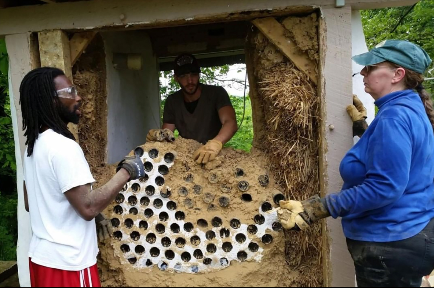 Three men working on the earthship together