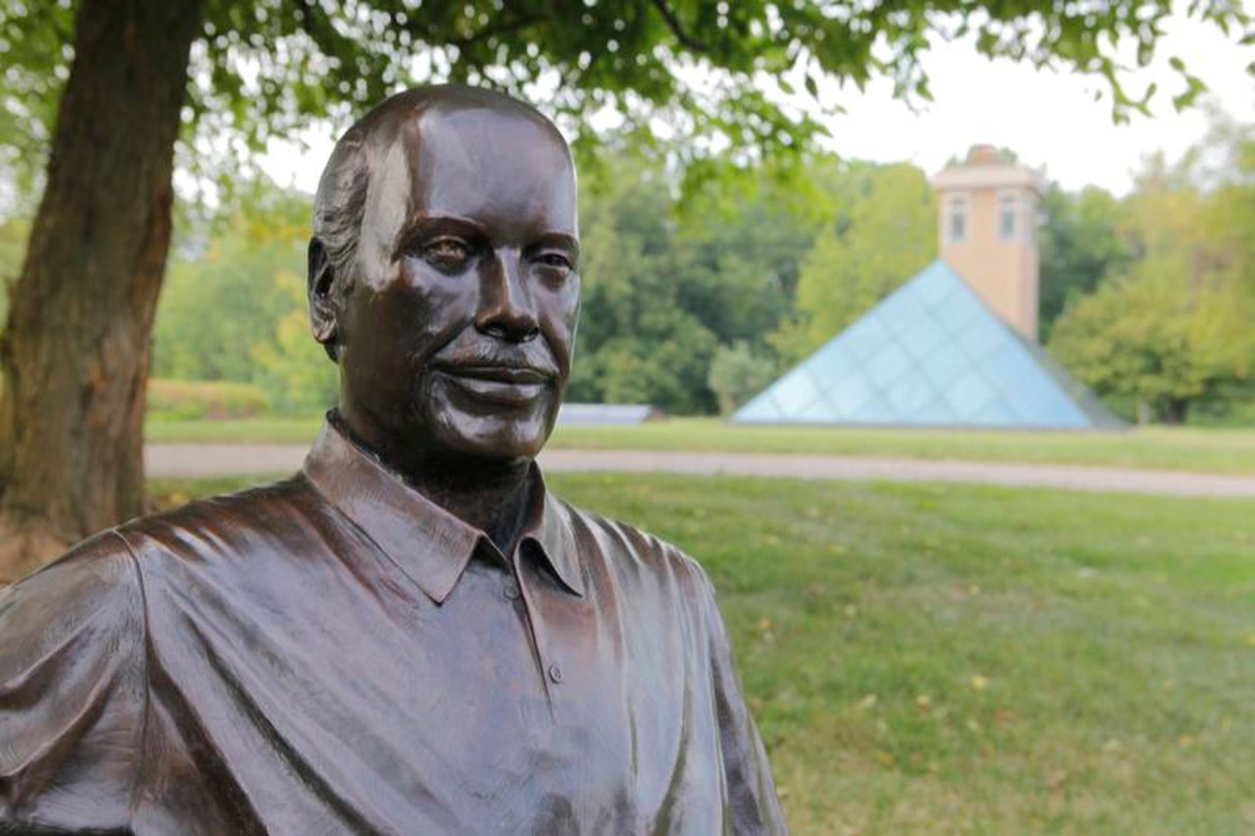 A statue of a man in the foreground, and in the back is the Pyramid House. Lots of green grass and trees in Ohio.
