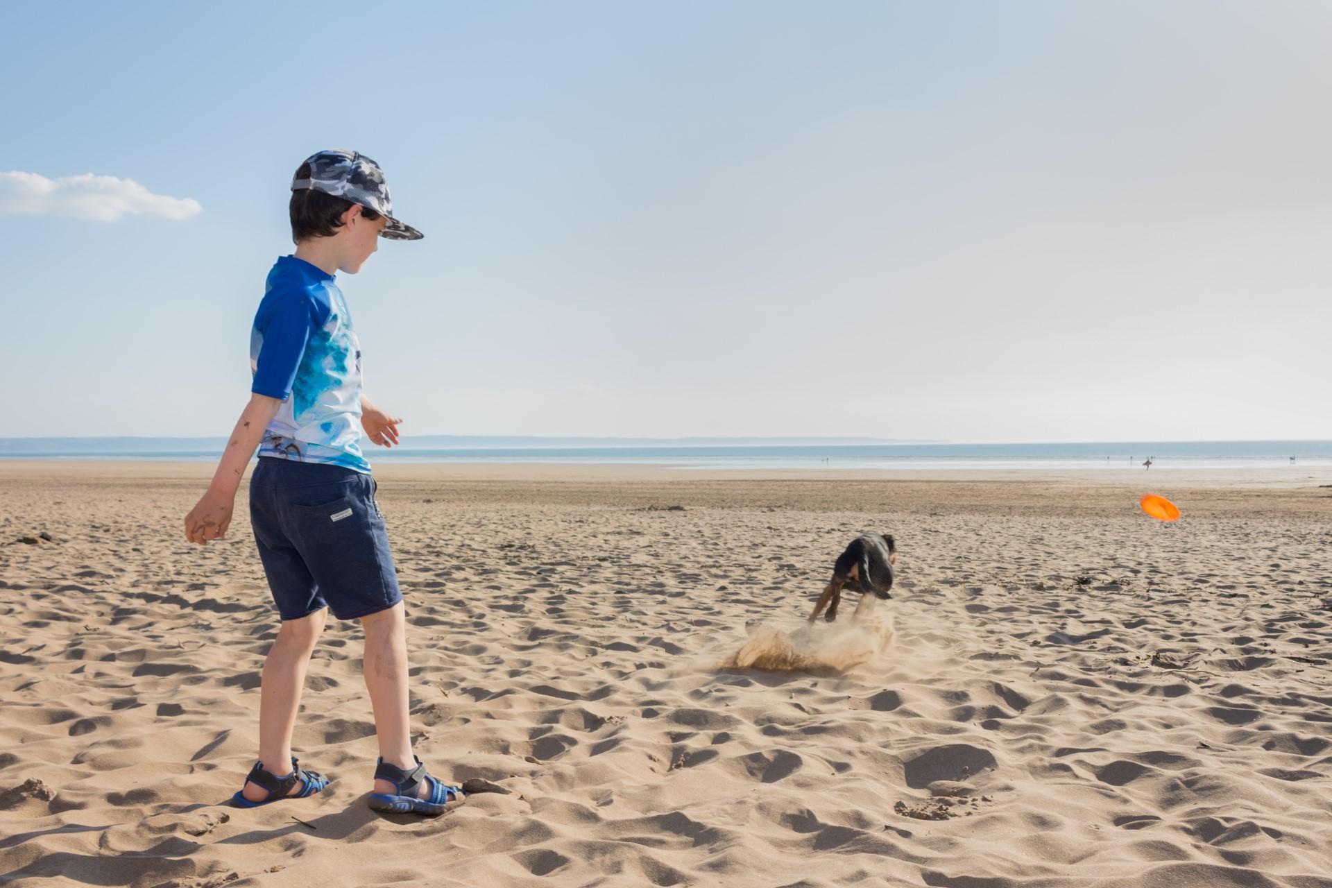 Boy playng with dog on Saunton Sands beach