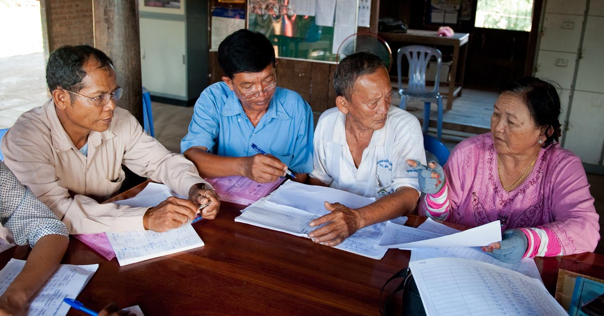 Commune council members meet to review the final draft list of poor households for each village.