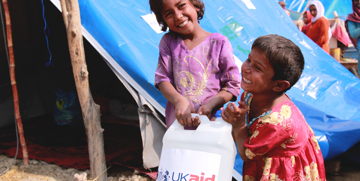 Children carry a bottle of detergent supplied by UKaid from the British government, as part of the UK's response to floods in Pakistan. Photo by DFID via Flickr, licensed under (CC BY 2.0).