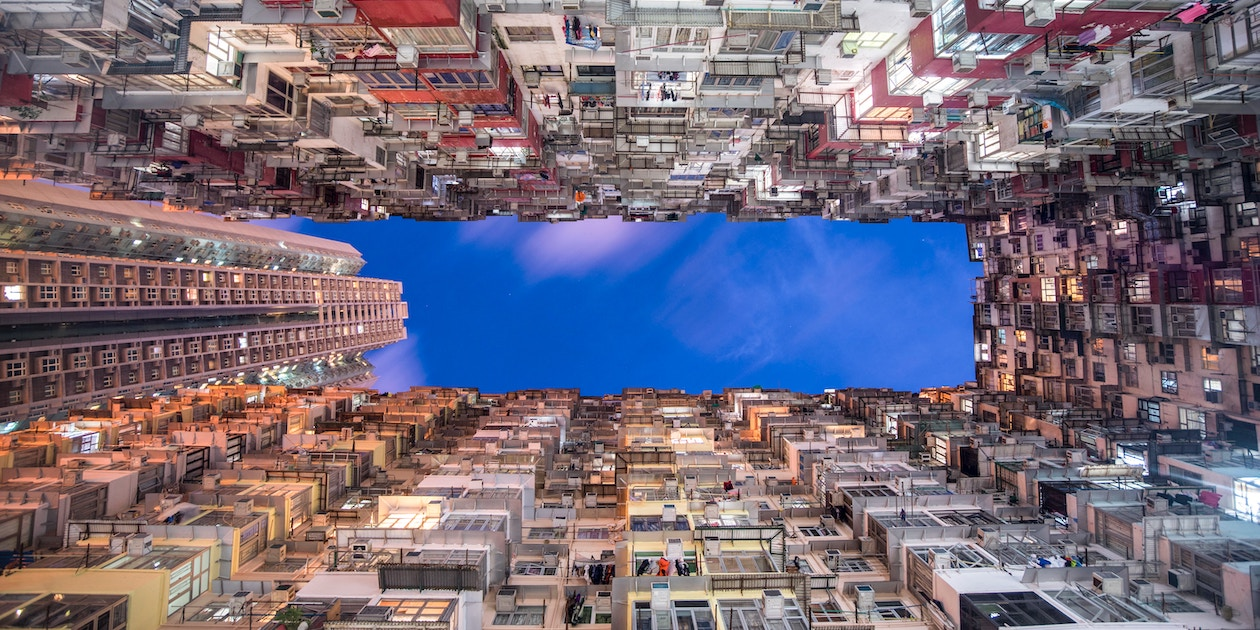 "The densely crowded, colorful apartment blocks of Hong Kong's so-called ""Monster Building,"" built in the 1960s, contrast with a more modern high-rise apartment building on the left. Photo by Denis Ng on Unsplash."