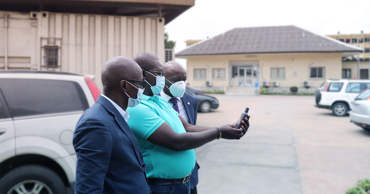 Health officials in Abidjan Côte d'Ivoire examine a global positioning system device