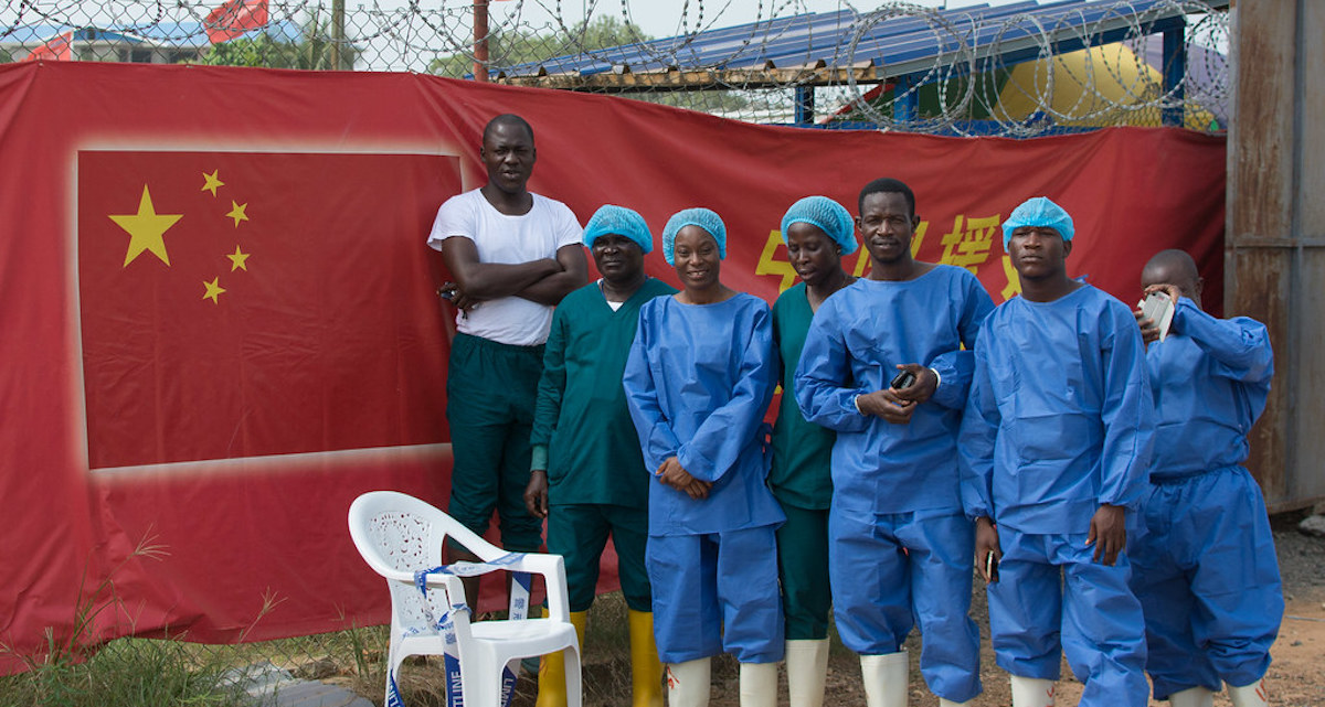 Ebola Response workers stand outside the Chinese Ebola treatment unit (ETU) in Monrovia, Liberia, during a ceremony as Liberia's last Ebola patient was released on 5 March 2015