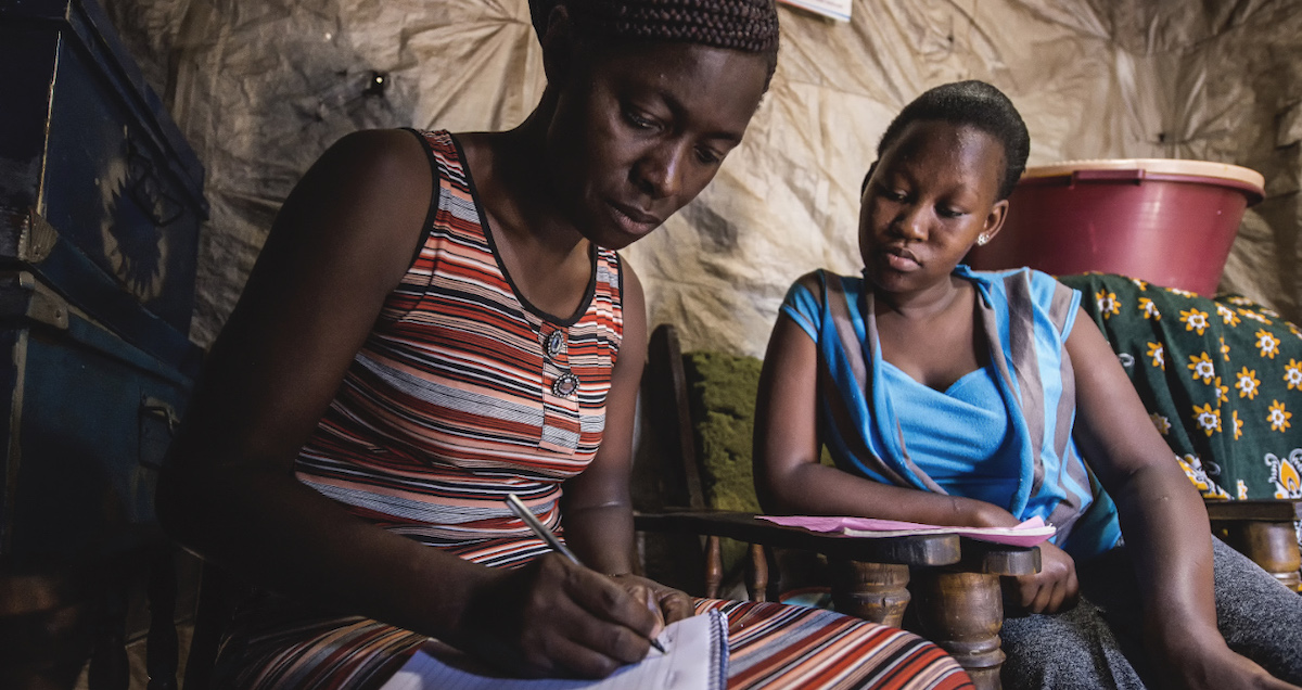 A community healthcare worker takes records of a patient's wellbeing. Photo by APHRC, used with permission.