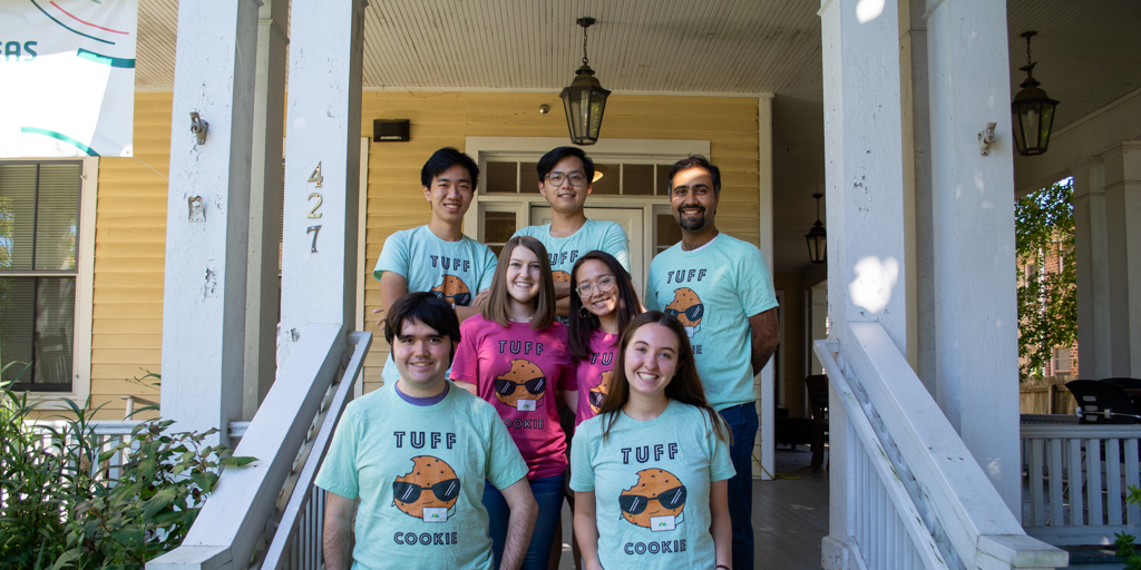TUFF team staff and student research assistants stand on the porch of the Global Research Institute in their TUFF Cookie team shirts. Back row: Andy Shufer, Sailor Miao, and Dr. Ammar Malik (Senior Research Scientist and head of AidData's China Development Finance Program). Middle row: Kyra Solomon (Junior Program Manager) and Thai-Binh Elston (Junior Program Manager). Bottom row: Rory Fedorochko and Sam Rofman. Photo by Carla Talbert/GRI, all rights reserved.