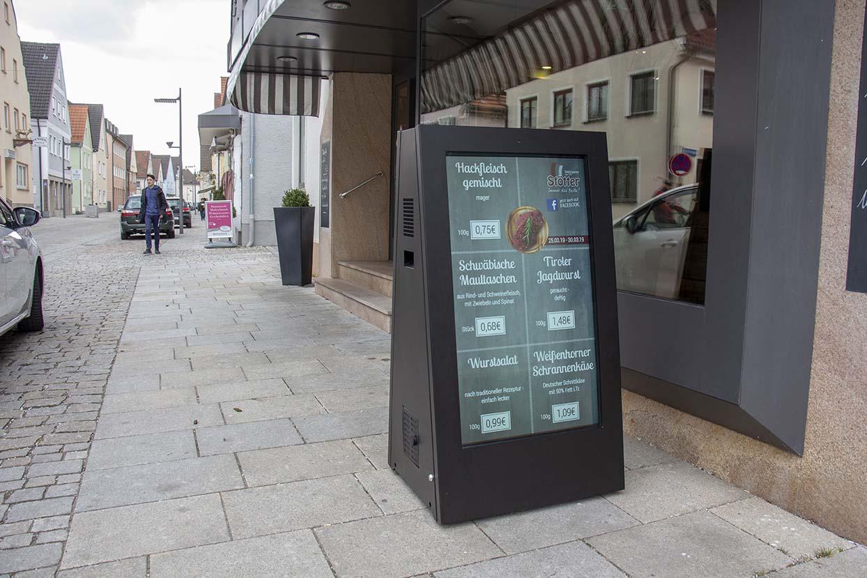 Ein digitaler Kundenstopper von Wedeko, genannt eStopper, vor einem Ladengeschäft
