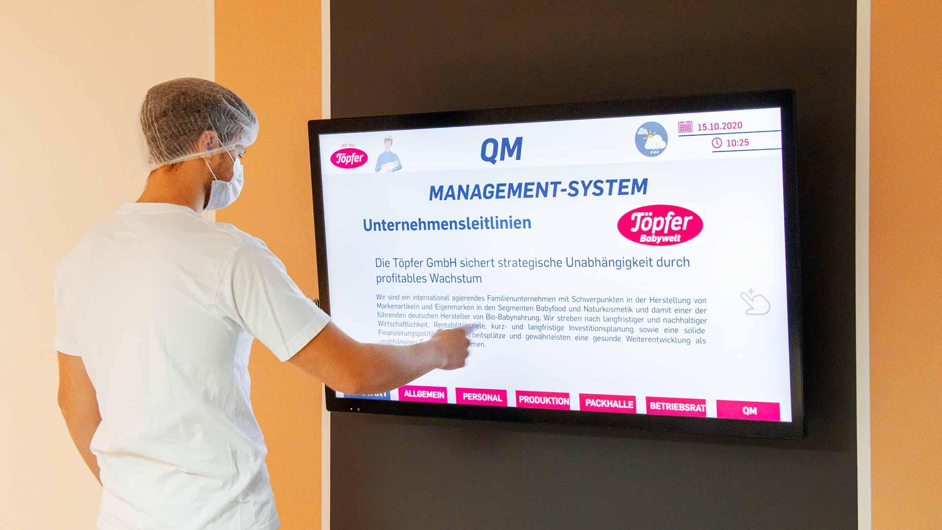 Mitarbeiter vor einem digitalen Infosystem, auch Digital Signage genannt. Mit Touch-Funktion.