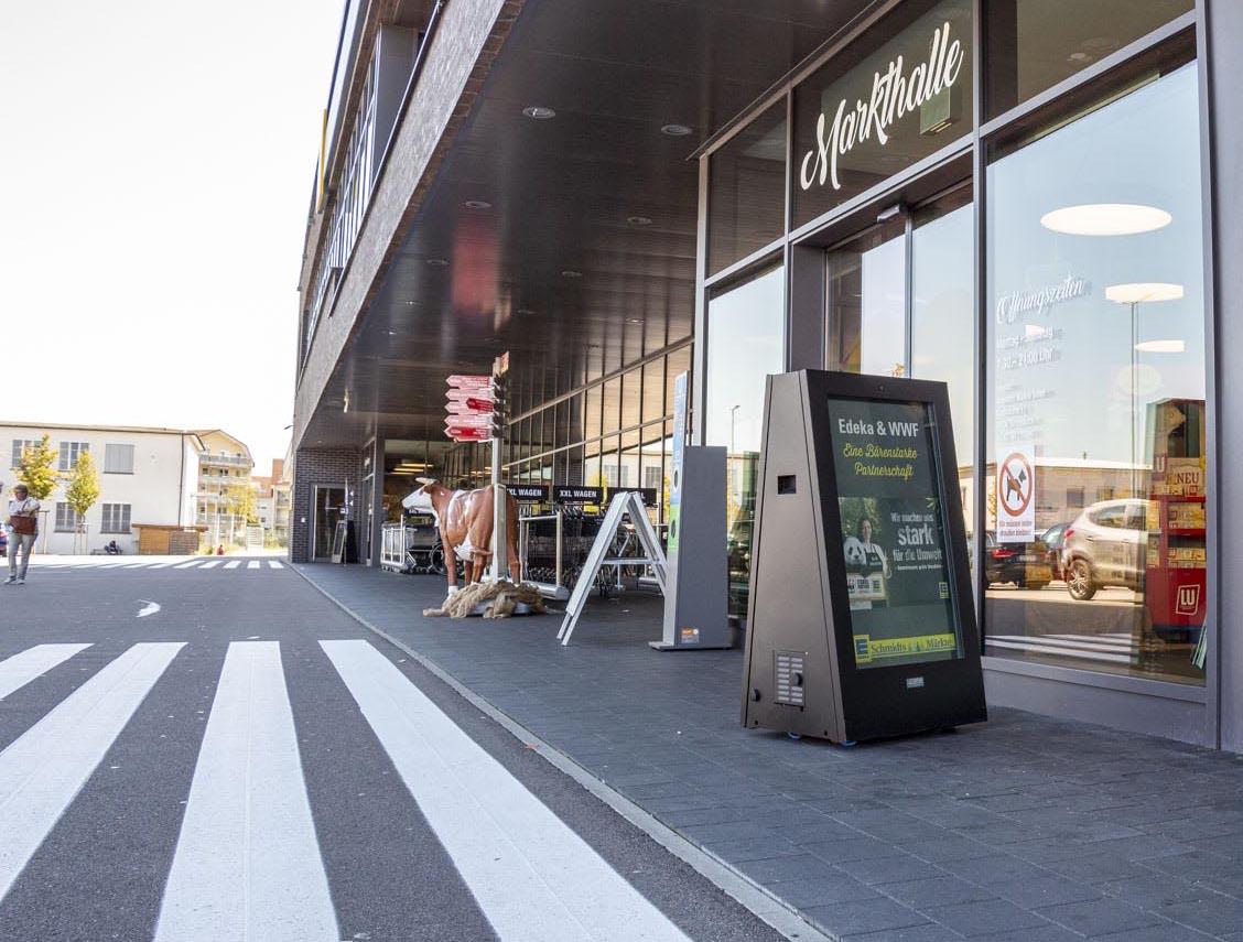 Digitaler Kundenstopper - eStopper - vor einem Supermarkt
