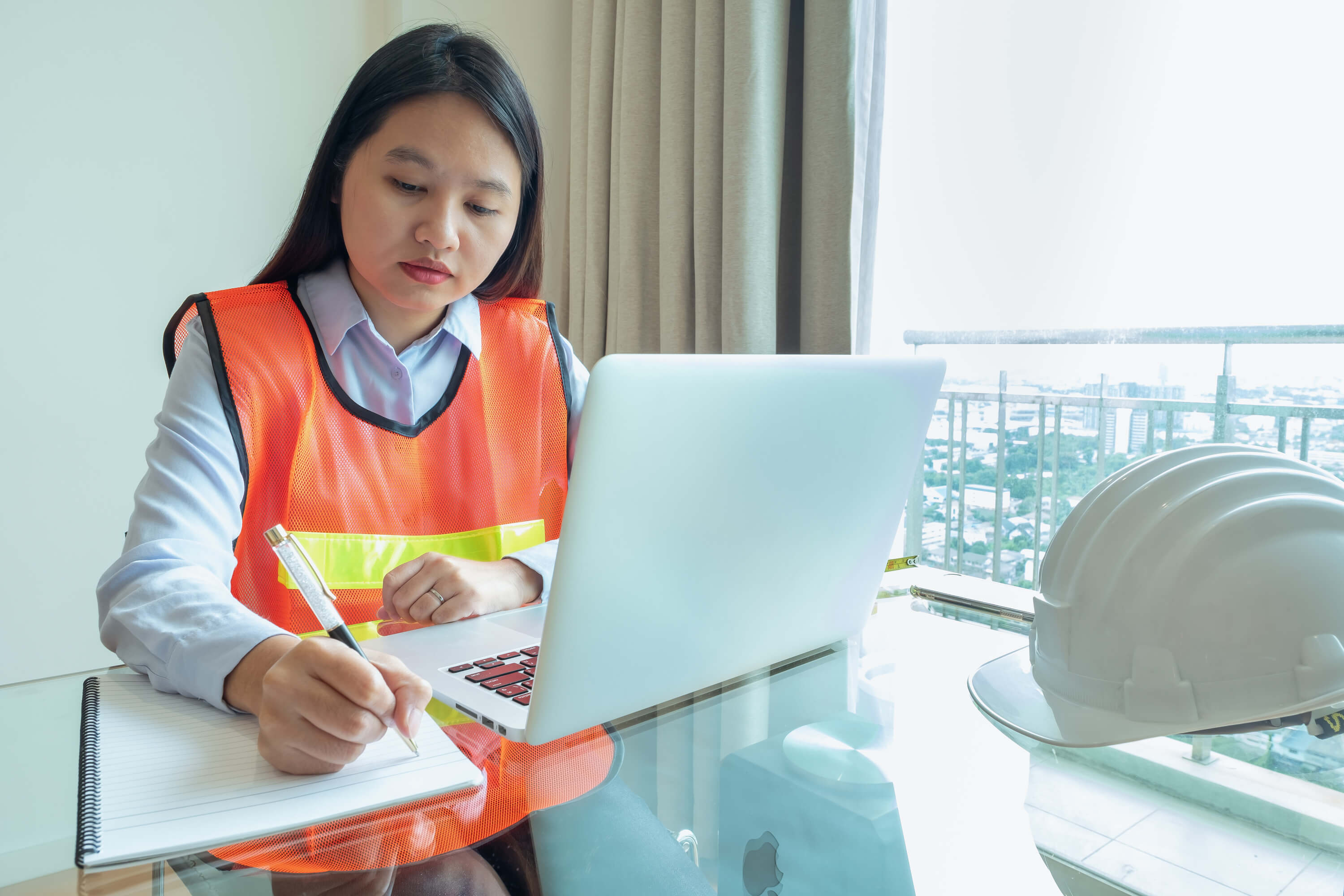 Female maintenance worker in construction orange vest writing notes from a laptop computer Photo