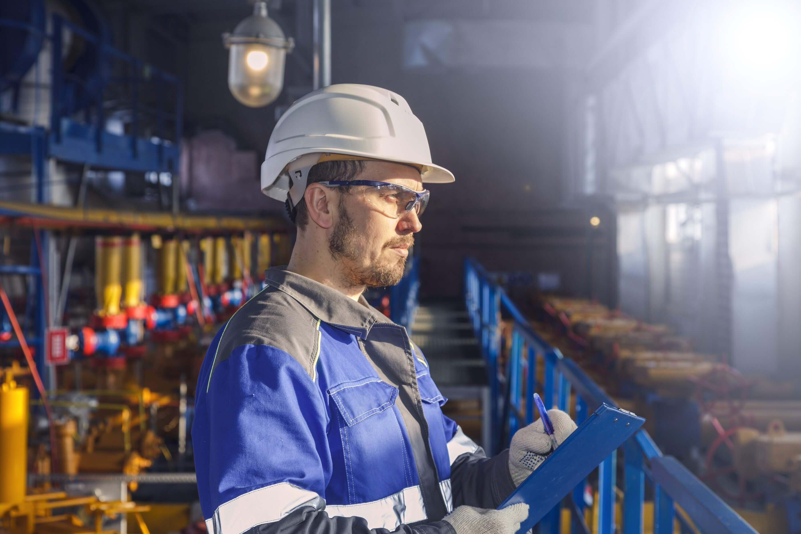 maintenance man in blue uniform and hard hat looking off into distance. Photo