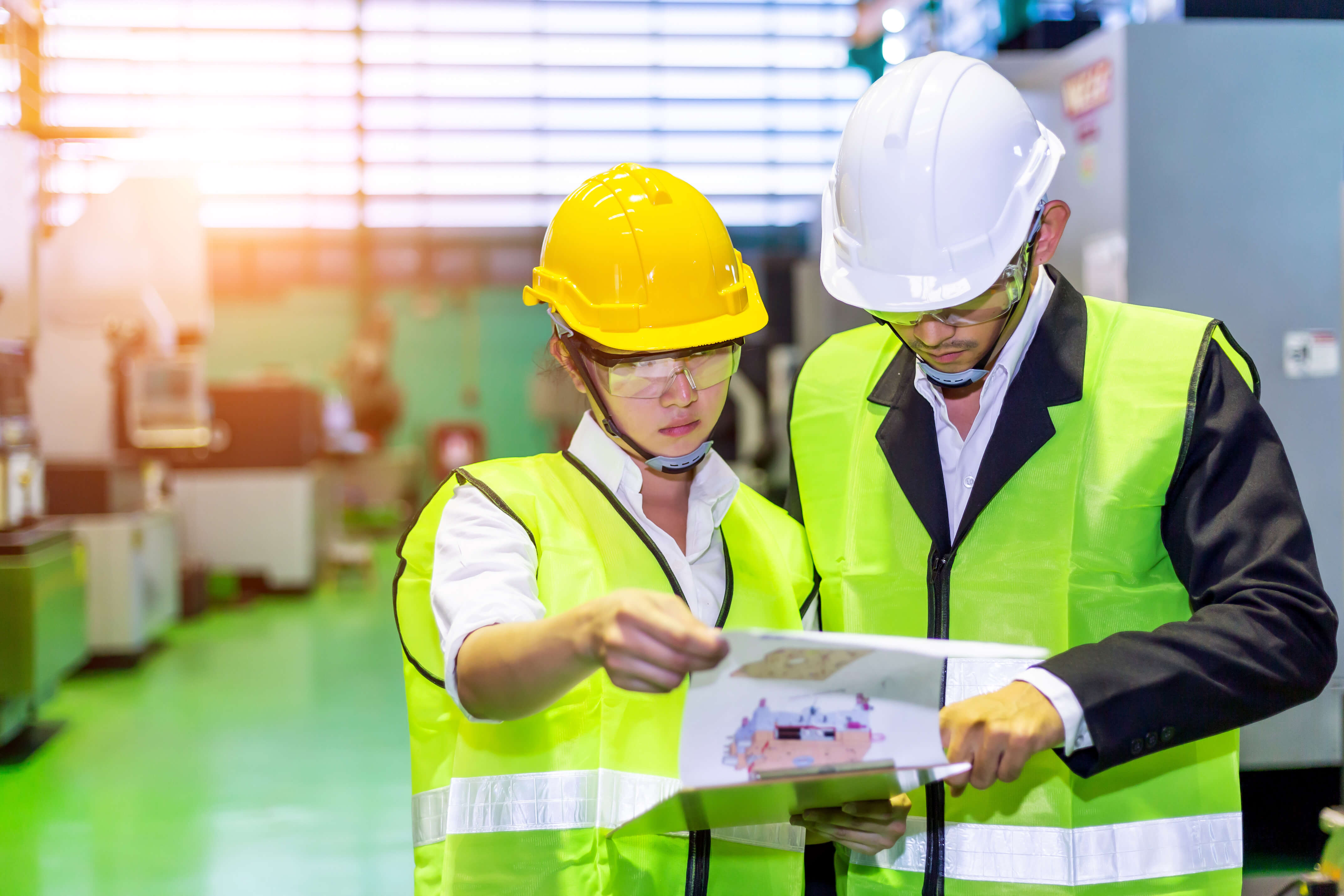 Male and female maintenance worker holding plans in maintenance setting. Photo