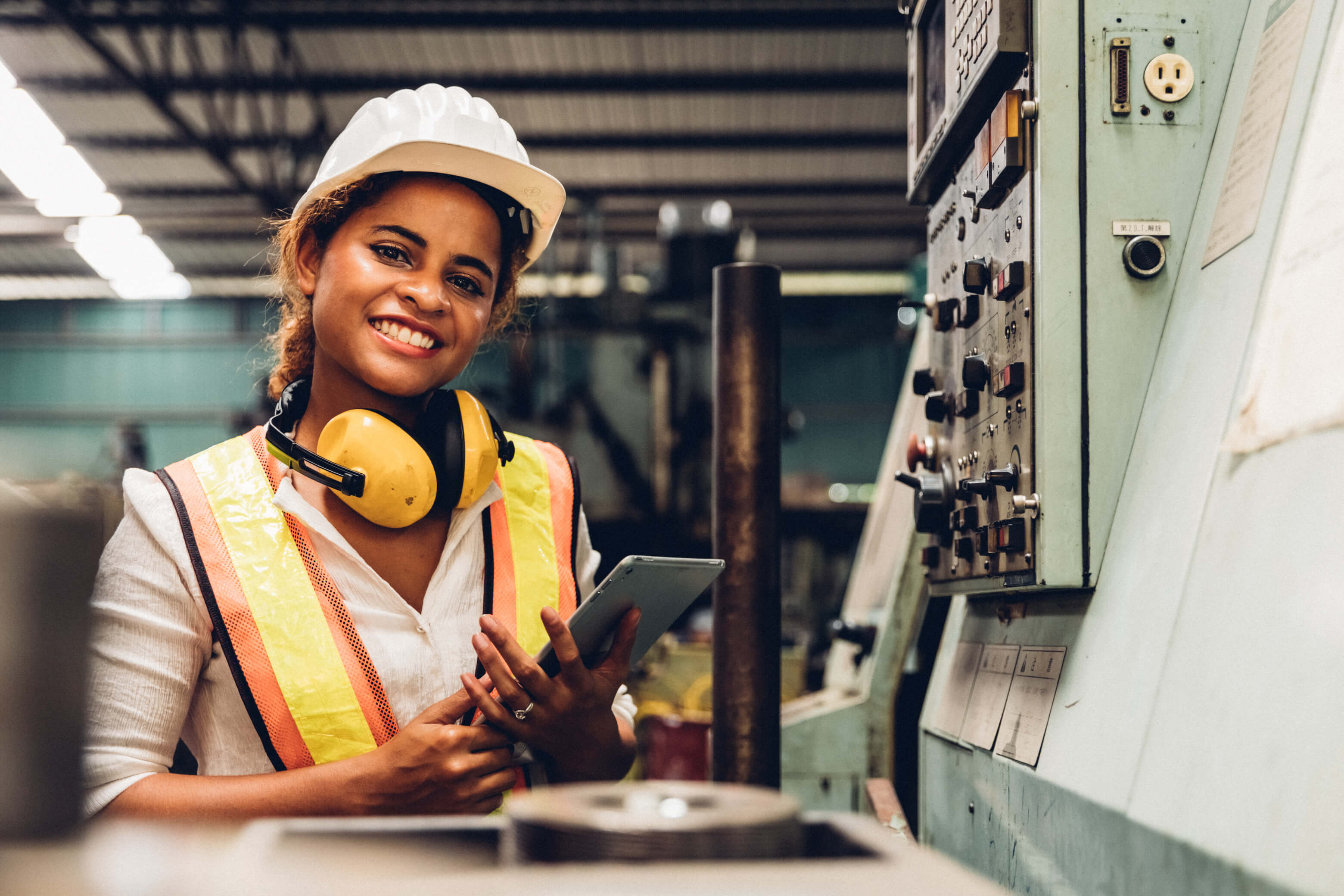 Female maintenance worker in a factory smiling and holding tablet