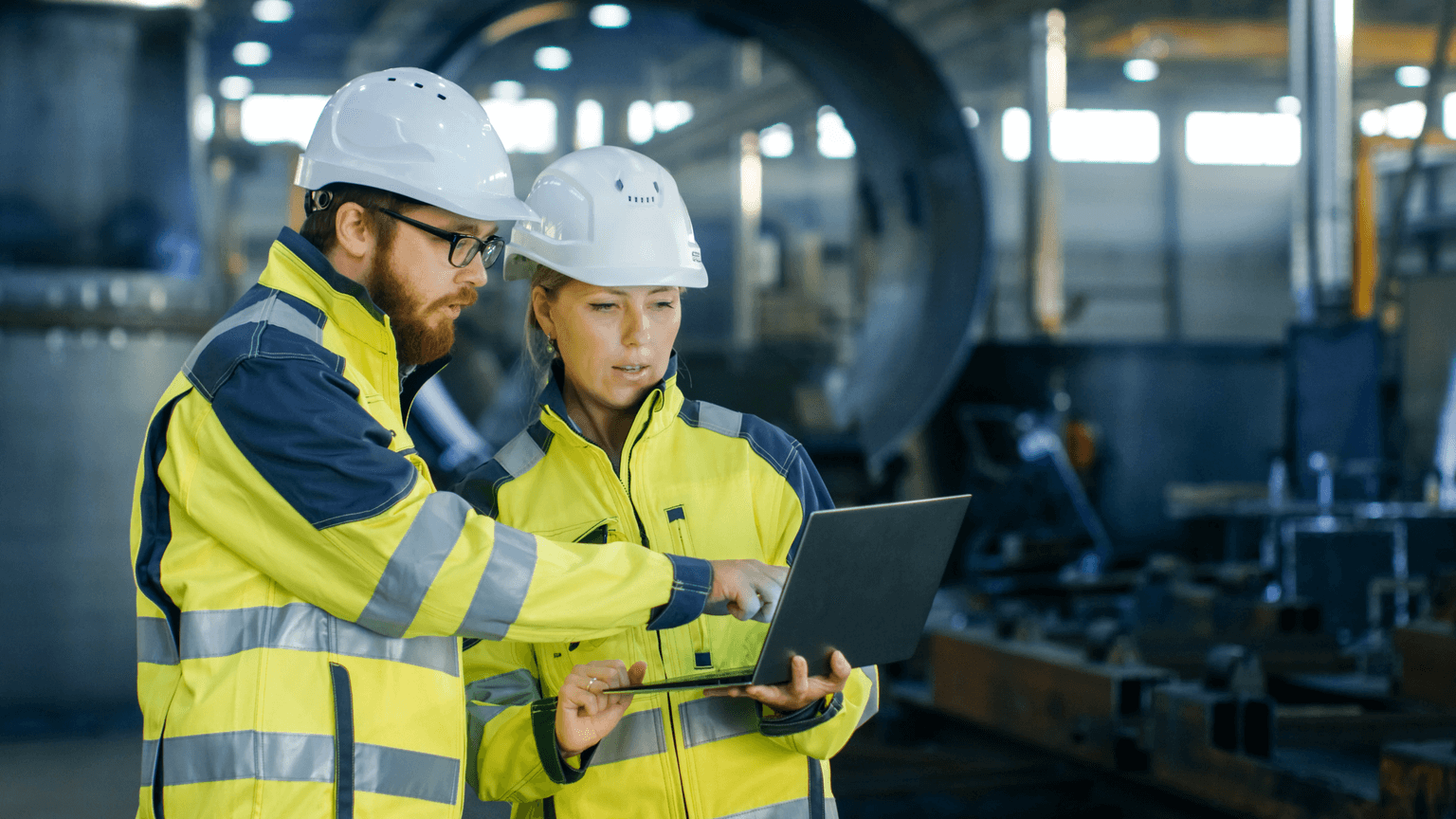 Male and female maintenance workers in a factory wearing hard hats and yellow reflective uniforms, holding a laptop. Photo