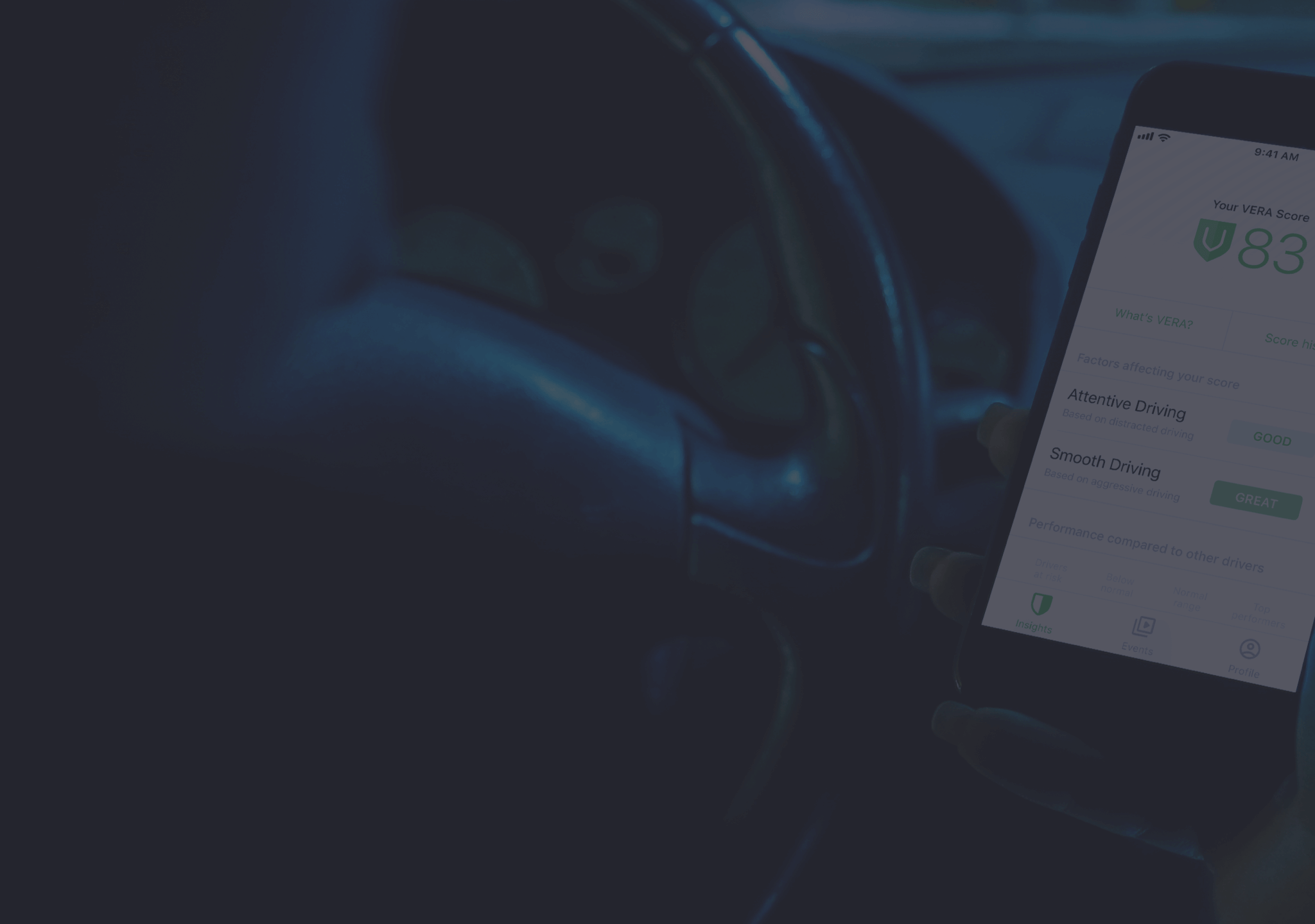 Photo of a driver in a car holding a mobile phone showing the Nauto mobile app