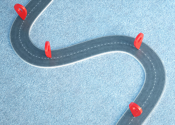 Overhead view of a toy road on a mottled blue surface. On the road are four red location markers spaced at random intervals.