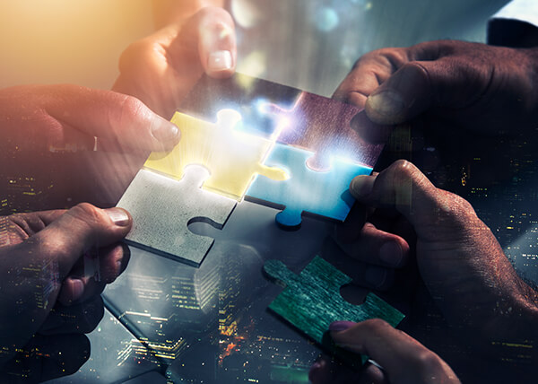 Close-up of a group of hands bringing six puzzle pieces together, glowing where the sides of each touch.