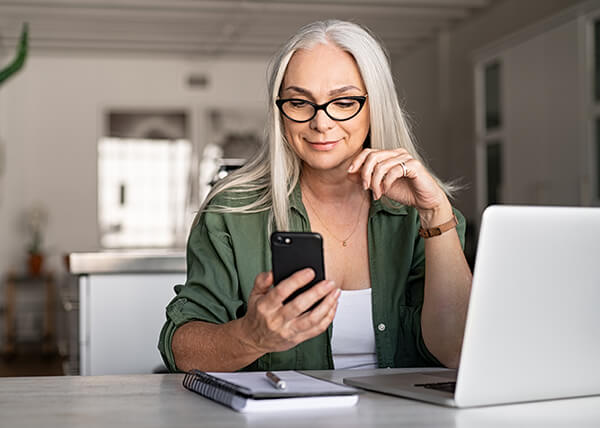 Mature woman with long white hair wearing glasses and looking at her mobile phone.