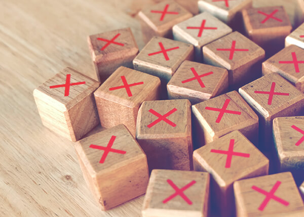 A pile of small wooden cubes, each with a red X printed on top.