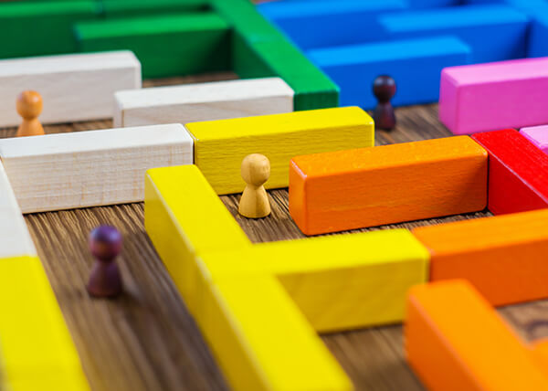 Colorful blocks set out on a wooden surface, creating a maze. In the maze are several wooden figures, placed in different sections.