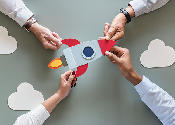 A paper cutout of a rocket being held up by 4 different hands.