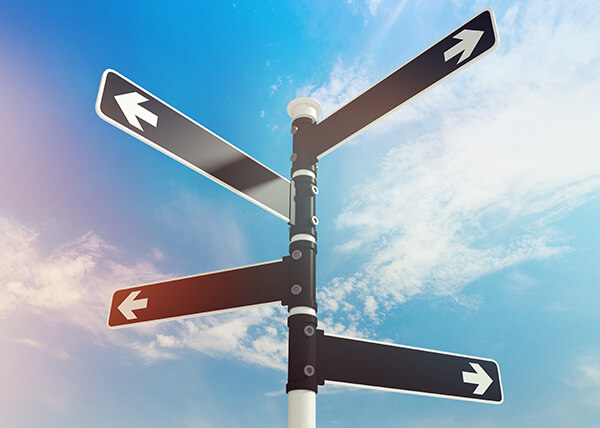 Sign post against a partly-clouded blue sky. The post has 4 black signs and each one has a single white arrow, pointing outward.