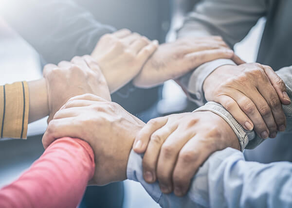 Close-up of a group's hands. Each person is holding onto the wrist of the person beside them to form a circle.